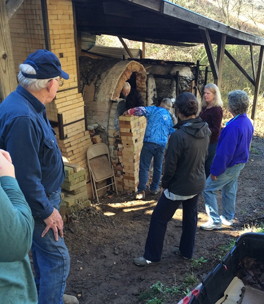 The community helps to unload the kiln, fire brigade style.